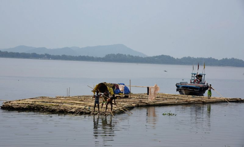 Indian vendors steer a bamboo pontoon along the Brahmaputra river in Guwahati on June 1, 2017.