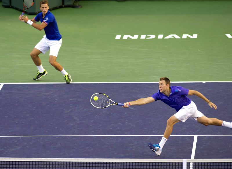 Vasek Pospisil of Canada and Jack Sock (R) of the United States compete during the men's double final match against Italy's Simone Bolelli and Fabio Fognini ...