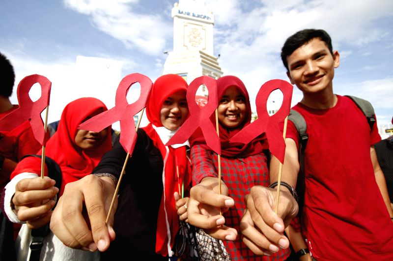 Indonesian Muslim students hold red ribbons to mark the World AIDS Day in Aceh, Indonesia, Dec. 1, 2015.