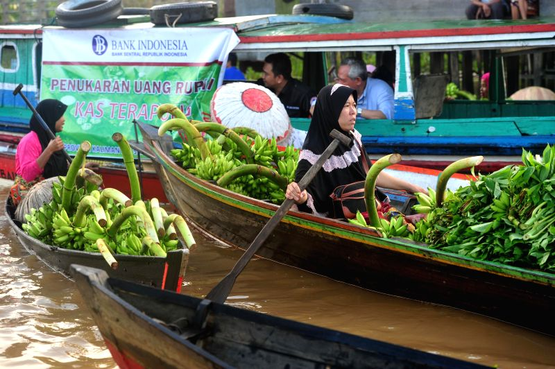 Indonesian women in wooden boats sell fresh fruits and vegetables at the Lok Baintan floating market in Banjar, South Kalimantan province, Indonesia, May ...