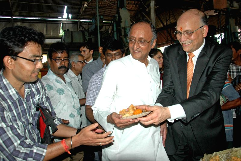 Industrialist and owner of Jessop, Pawan Ruia, Industry Minister Amit Mitra serving snakes to worker during Jessop factory re-open after three month in Kolkata on Aug 9, 2014. - Amit Mitra