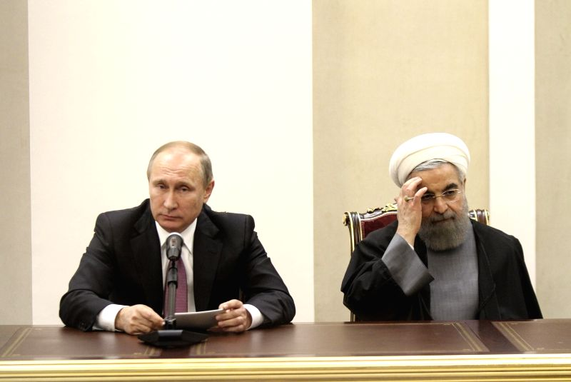 Iranian President Hassan Rouhani (R) and his Russian counterpart Vladimir Putin hold a press conference after their meeting following the third summit of the Gas ... - Hassan Rouhani