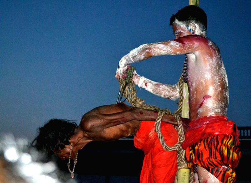 Iron hooks being pierced in the back of a devotee who is going to be hanged during celebration of Charak festival in Tripura April 14, 2014. Charak is celebrated to please Lord Shiva, the Hindu god ..