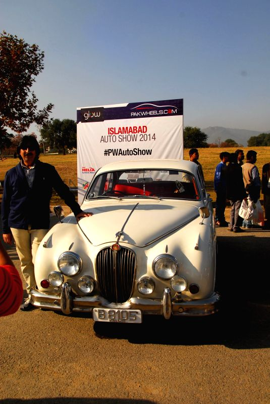 A visitor poses for a photo with a vintage car during the 3rd Islamabad Auto Show in Islamabad, capital of Pakistan on Nov. 23, 2014. The third Islamabad Auto Show 2014 orchestrated by ...