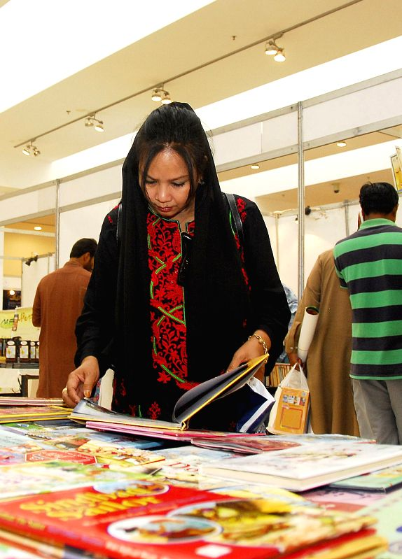ISLAMABAD, April 23, 2017 - A woman reads a book at a stall during 8th National Book Fair in Islamabad, capital of Pakistan, on April 23, 2017. The World Book Day falls on Sunday. (Xinhua/Saadia ...