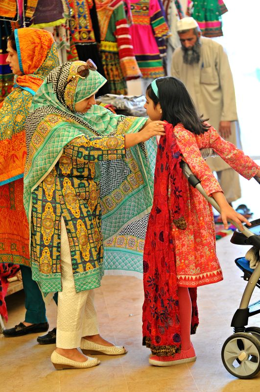 ISLAMABAD, April 30, 2017 - A woman tries a dress on her daughter on the last day of Fashion Expo 2017 in Islamabad, capital of Pakistan, on April 30, 2017. Over 100 exhibiters participated during ...