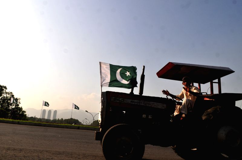 A man rides on a tractor decorated with Pakistani national flag ahead of forthcoming celebrations for the country's Independence Day in Islamabad, capital of ...