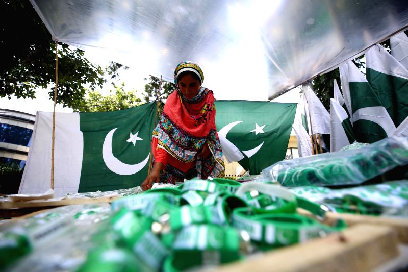 ISLAMABAD, Aug. 11, 2018 - A Pakistani woman selects national flag at a roadside stall ahead of the country's independence day in Islamabad, capital of Pakistan, on Aug. 11, 2018. Pakistan will ...