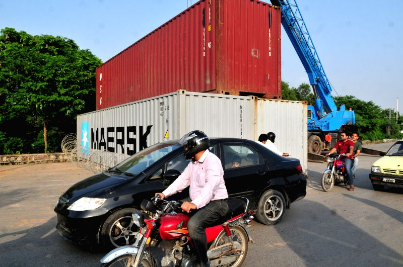 A road is blocked by a shipping container on a highway in Islamabad, capital of Pakistan, Aug. 14, 2014. A Pakistani cabinet minister said on Thursday that ...