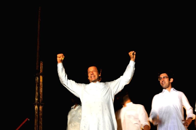 Senior Pakistani political leader Imran Khan (C) gestures as he arrives at a protest march in Islamabad, capital of Pakistan, Aug. 15, 2014. Thousands of ... - Imran Khan