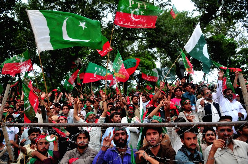 Supporters of Pakistani political leader Imran Khan wave flags as they take part in a protest against the country's ruling Pakistan Muslim League-Nawaz in ... - Nawaz Sharif and Imran Khan