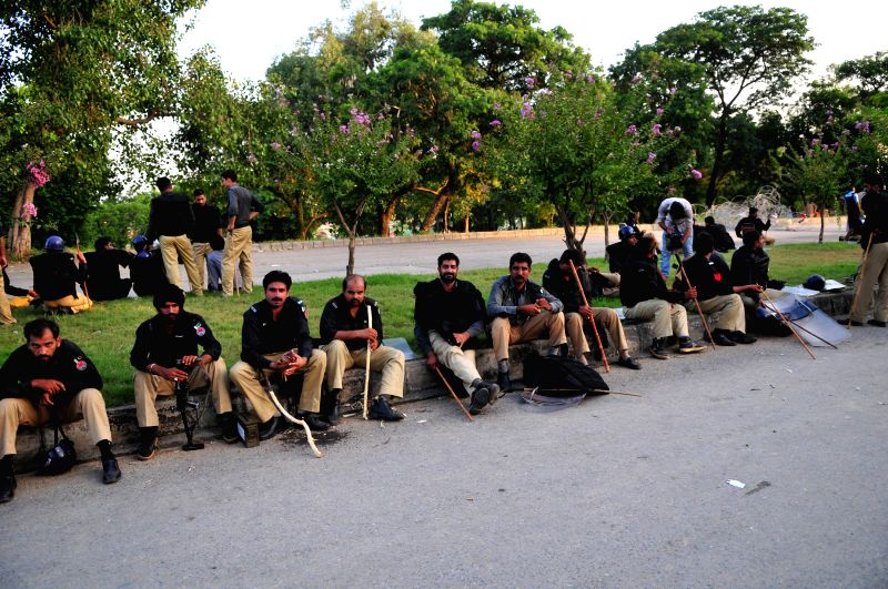 Riot police rest on road during a protest march in Islamabad, capital of Pakistan on Aug. 19, 2014. Pakistan's interior minister says that army troops are being ..