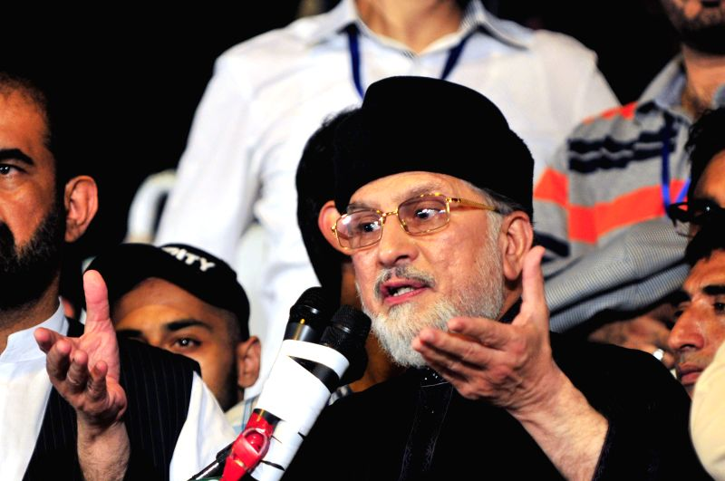 Pakistani anti-government leader Tahir-ul-Qadri addresses demonstrators in front of the Parliament during an anti-government protest in Islamabad, capital of ... - Nawaz Sharif