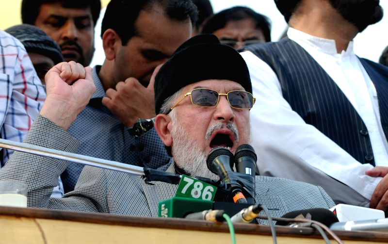 Pakistani anti-government leader Tahir-ul-Qadri delivers a sermon for congregational Friday prayers held at an anti-government protest site in front of the ...