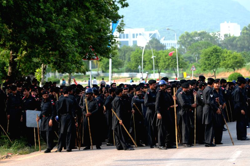 Pakistani policemen stand guard during a protest in Islamabad, capital of Pakistan, Aug. 21, 2014. Pakistani parliament on Thursday unanimously passed a ... - Nawaz Sharif