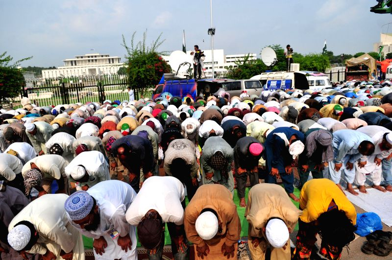 Supporters of Pakistani anti-government leader Tahir-ul-Qadri pray during a congregational Friday prayers held at an anti-government protest site in front of the .