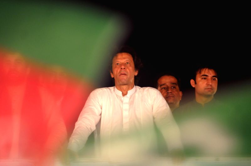Imran Khan (L), head of opposition political party Pakistan Tehrik-e-Insaf, looks during an anti-government protest for the 12th day in Islamabad, capital of ...