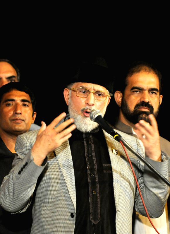 Religious leader Tahir-ul-Qadri speaks to supporters during an anti-government protest in front of the parliament building in Islamabad, capital of Pakistan, on ..