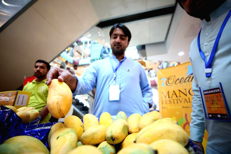 ISLAMABAD, Aug. 3, 2018 - A vendor holds a mango at a stall during mango festival in Islamabad, capital of Pakistan on August 3, 2018. A three-day mango festival kicked off in Islamabad on Friday, ...