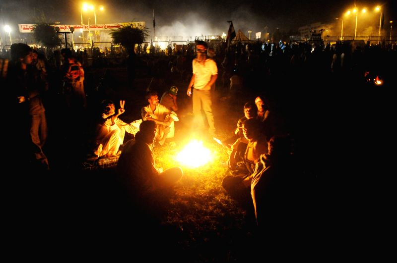 Pakistani protestors sit around fire following clashes near the prime minister's residence in Islamabad, capital of Pakistan on Aug. 31, 2014.  At least 450 ...