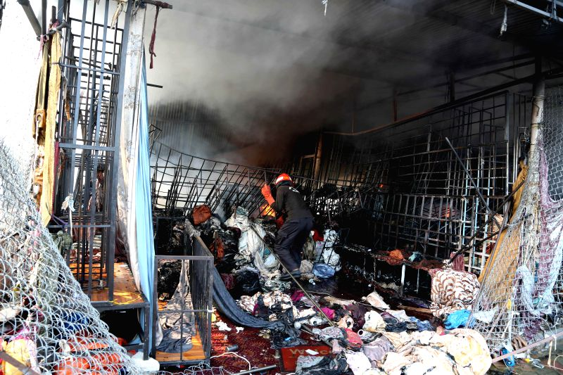 ISLAMABAD, July 18, 2018 - A firefighter tries to extinguish fire at the fire site in Islamabad, capital of Pakistan, on July 18, 2018. At least 150 shops were gutted in a high-intensity fire that ...