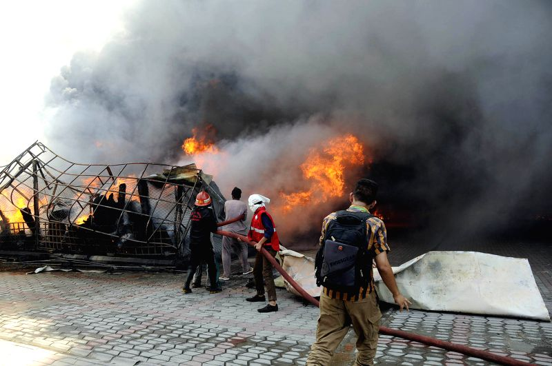 ISLAMABAD, July 18, 2018 - Firefighters try to extinguish fire at the fire site in Islamabad, capital of Pakistan, on July 18, 2018. At least 150 shops were gutted in a high-intensity fire that broke ...