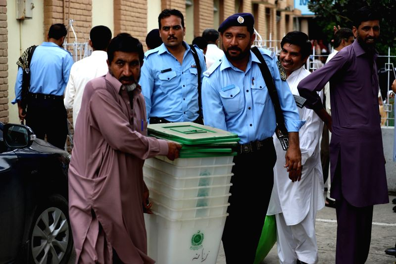 ISLAMABAD, July 24, 2018 - Policemen carry ballot boxes at a distribution center in Islamabad, capital of Pakistan, on July 24, 2018. Pakistan will hold its general elections on July 25.
