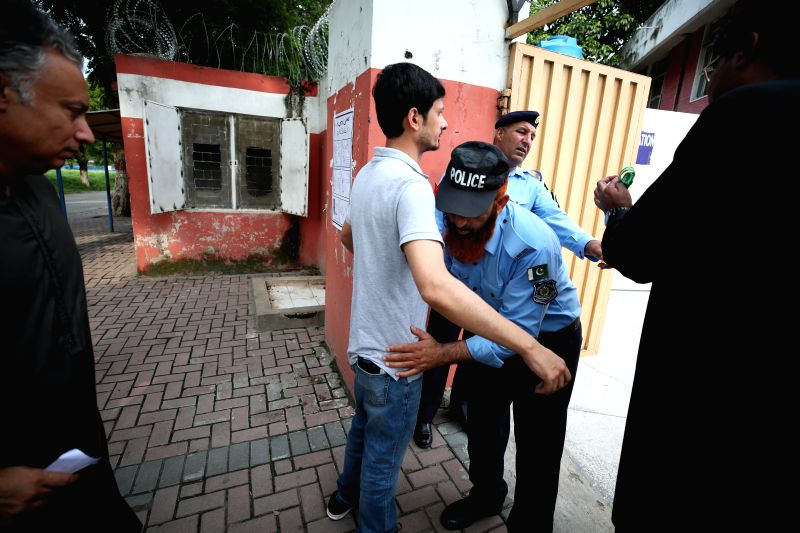 ISLAMABAD, July 25, 2018 - A policeman checks a voter outside a polling station in Islamabad, capital of Pakistan, on July 25, 2018. Pakistanis started casting votes in the country's one-day general ...