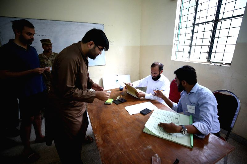 ISLAMABAD, July 25, 2018 - Election officials check data of voters at a polling station in Islamabad, capital of Pakistan, on July 25, 2018. Pakistanis started casting votes in the country's one-day ...