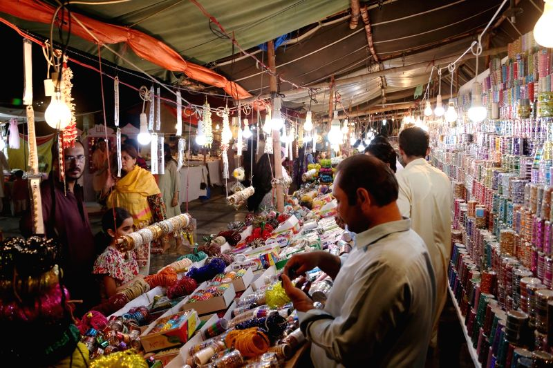 ISLAMABAD, June 13, 2018 - People go shopping at a local market ahead of Eid al-Fitr during the last week of Ramadan in Islamabad, capital of Pakistan, on June 12, 2018. Eid al-Fitr marks the end of ...
