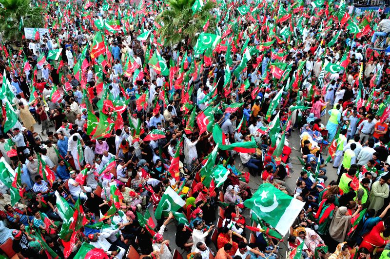 Supporters of Pakistan Tehreek-e-Insaf (PTI) wave party flags