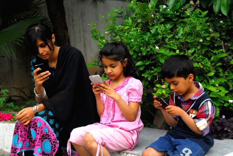Pakistani children play with cell phones on World Telecommunication and Information Society Day in Islamabad, capital of Pakistan on May 17, 2014. World ...
