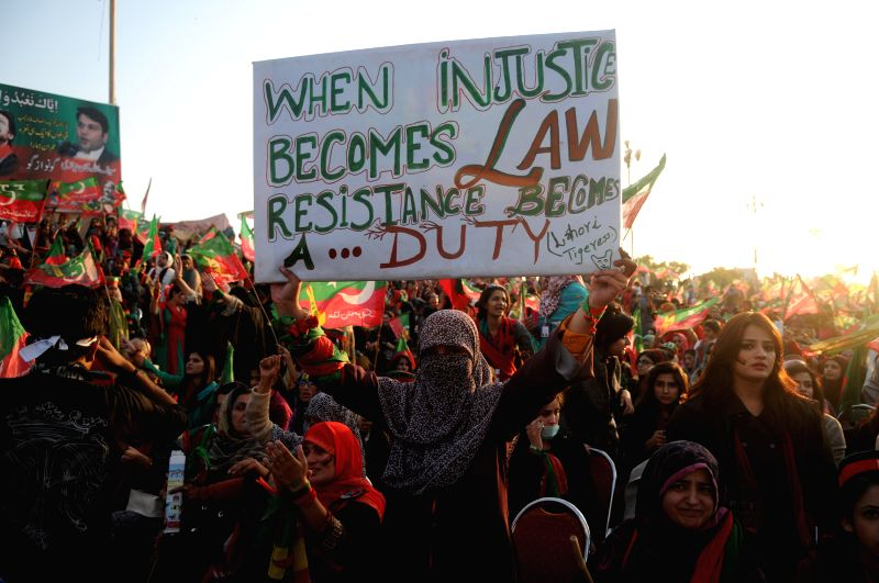 Islamabad (Pakistan): A supporter of Pakistan Tehrik-e-Insaf (PTI) or Justice Movement Party holds a placard during an anti-government rally in front of the Parliament in Islamabad, capital of ... - Imran Khan