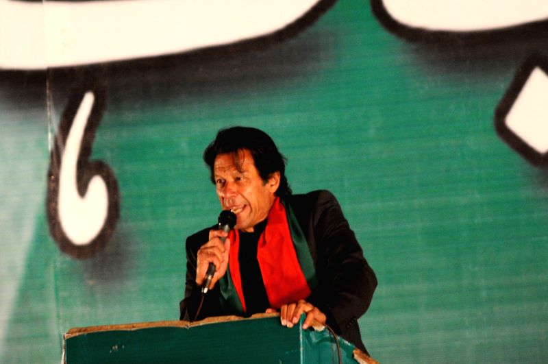 Islamabad (Pakistan): Imran Khan, leader of Pakistan Tehrik-e-Insaf (PTI) or Justice Movement Party, addresses his supporters during an anti-government rally in front of the Parliament in Islamabad, . - Imran Khan