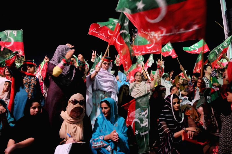 Supporters of Pakistan Tehrik-e-Insaf leader Imran Khan wave flags during an anti-government protest near the prime minister's residence in Islamabad, capital of . - Nawaz Sharif and Imran Khan
