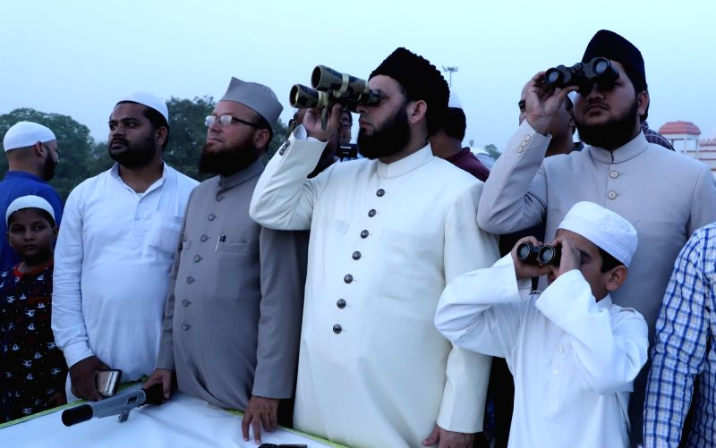 Islamic scholar and Imam-e-Eidgah Maulana Khalid Rasheed Firangi Mahali spots the Eid moon using binoculars, in Lucknow on June 14, 2018.