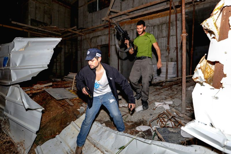 Israeli policemen search for a Palestinian attacker at a construction site in Kiryat Gat, southern Israel, on Nov. 21, 2015. A suspected terrorist stabbed and ...