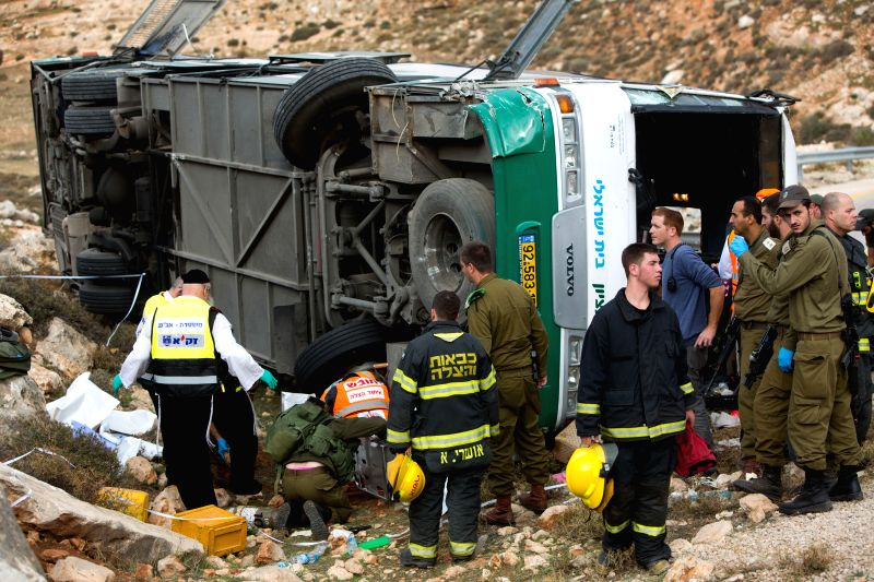 Israeli rescue staff work at the scene of a bus crash near the Kohav Hashachar Jewish settlement, northeast of Ramallah in the West Bank, on Nov. 26, 2015. An ...