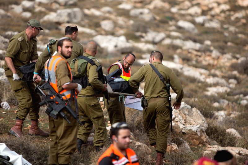 Israeli soldiers carry the body of a comrade killed in a bus crash at the scene near the Kohav Hashachar Jewish settlement, northeast of Ramallah in the West ...