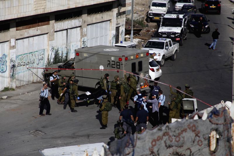 Israeli soldiers move the body of a Palestinian young man, who Israeli army said stabbed a soldier, in the West Bank city of Hebron on Oct. 29, 2015. The Israeli ...