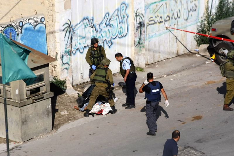 Israeli soldiers stand next to the body of a Palestinian young man, who Israeli army said stabbed a soldier, in the West Bank city of Hebron on Oct. 29, 2015. The ...
