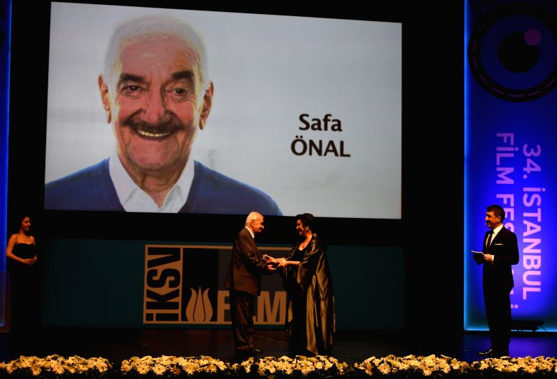 Turkish director Safa Onal(2nd L) is awarded Cinema Honorary Award at the opening ceremony of 34th Istanbul International Film Festival in Istanbul, Turkey, April ...