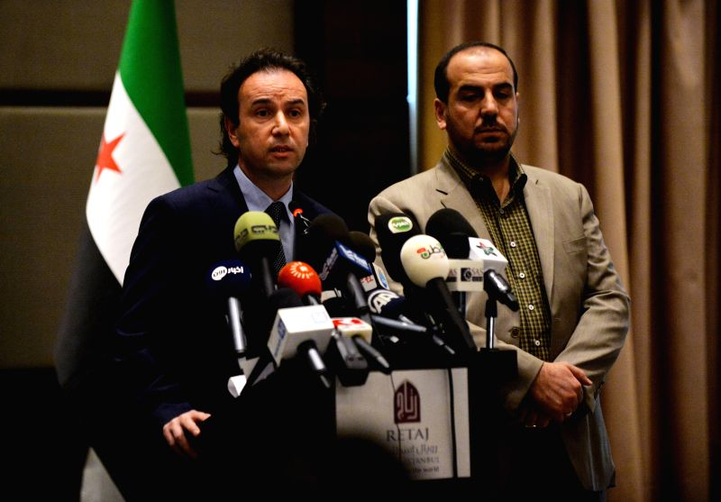 The newly elected president of Syria's main opposition National Coalition Khaled Khoja(L) delivers a speech at the press conference in Istanbul, Turkey, on Jan. 5, .