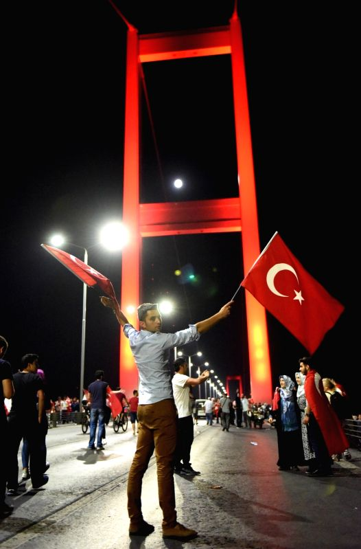 ISTANBUL, July 22, 2016 - A man waves Turkish flags as he attends a rally at the Bosphorus Bridge in Istanbul, Turkey, early July 22, 2016. Thousands of Turks gathered on Thursday night on the bridge ...