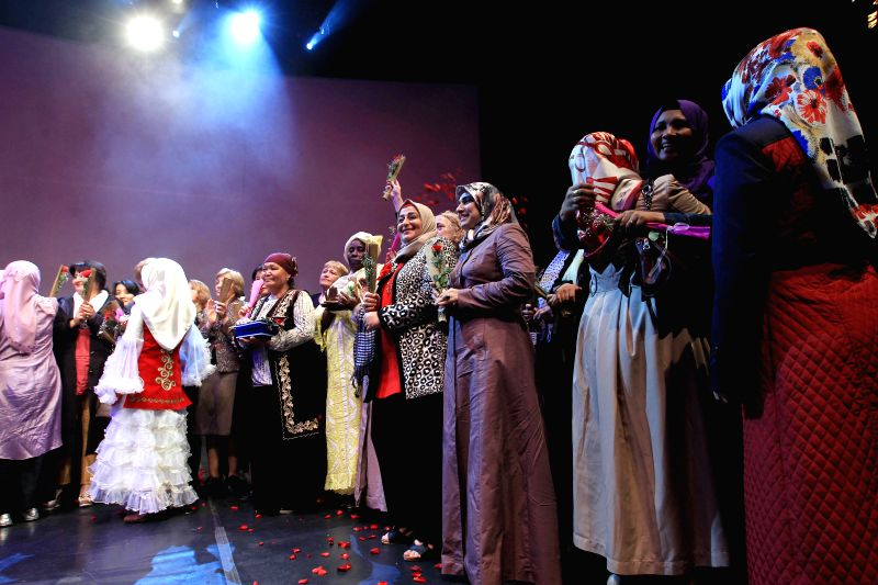 Mothers hold flowers to celebrate the Moher's day during the celebration in Istanbul, Turkey, May 10, 2014. A celebration for World Mother's Day brought 180 mothers