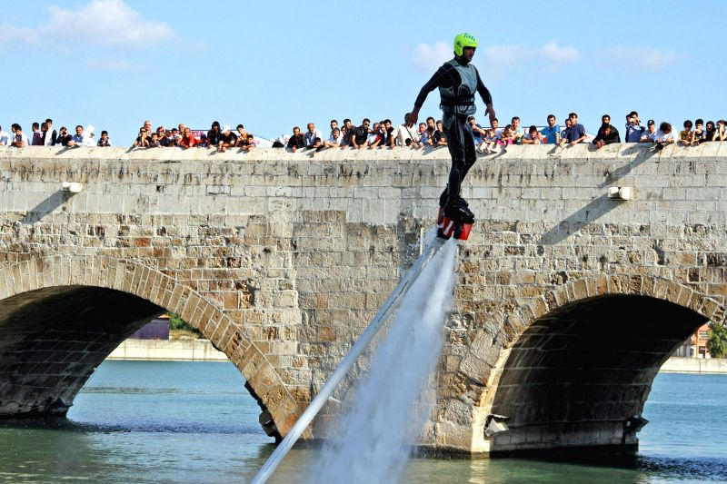 A stunt performer performs with water-propelled flyboard in Adana of Turkey on May 12, 2014. The engine with the applied water pressure can rise 7 meters high to ...