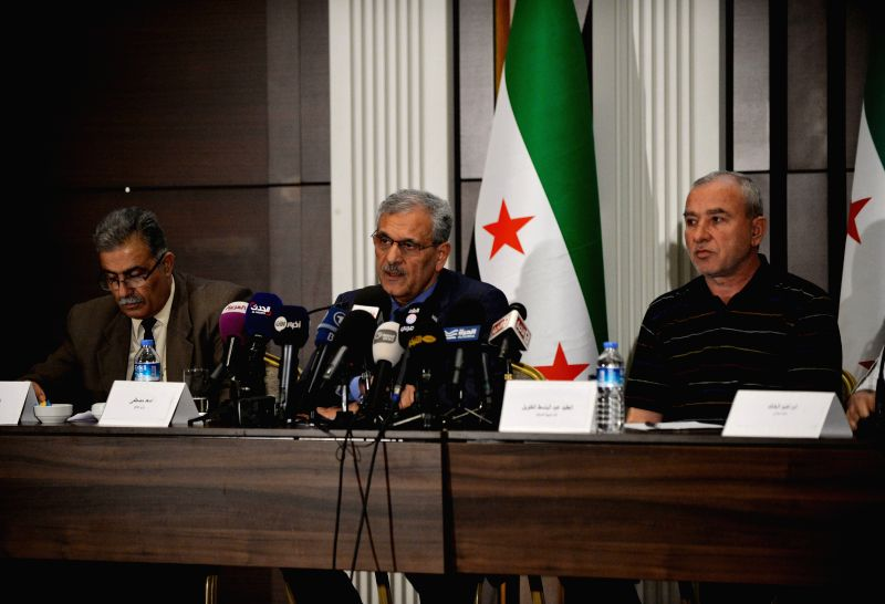 The Defense Minister of the Western-backed Syrian interim government Asaad Mostafa (C) gives a speech at a press conference in Istanbul on May 6, 2014. Syrian ...