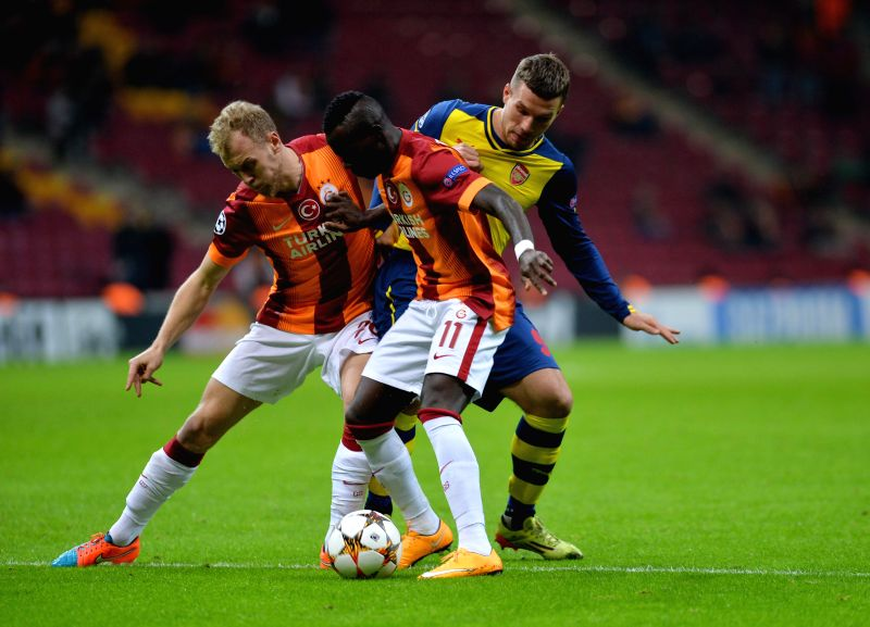 Istanbul (Turkey): Arsenal's Lucas Podolski (R) vies for the ball during the UEFA Champions League group D football match against Galatasaray at Ali Sami Yen Stadium in Istanbul, Turkey, on Dec. 9, ..