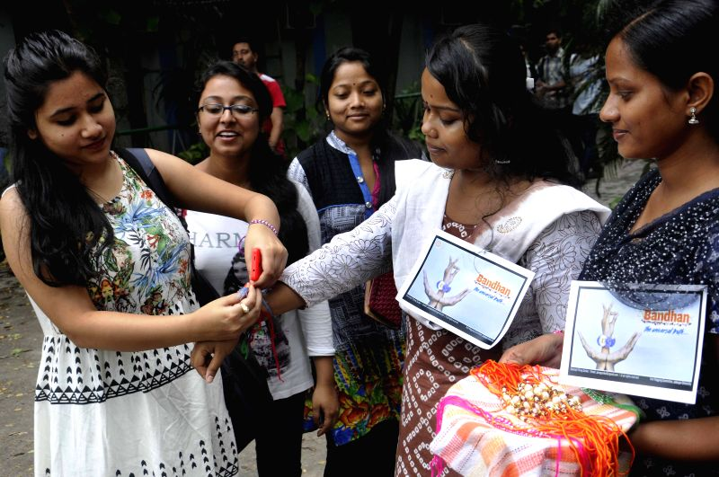 Jadavpur University students tie rakhis on the wrists of freshers as a part of anti-ragging campaign at the University in Kolkata, on July 27, 2015.