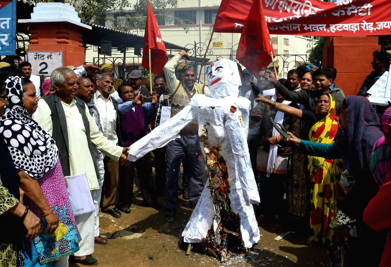 CPI(M) workers burn effigies of Rajasthan Chief Minister Vasundhara Raje as the protest against host of issues including hike in electricity tariffs and land acquisition ordinance in Jaipur, ... - Vasundhara Raje